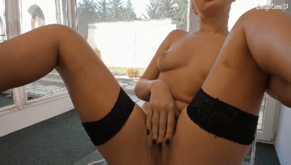 Naked woman masturbating near the window